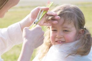 プロ用理美容はさみ国内生産本数No.1の家庭用髪はさみシゲルより先端のU字形状が安全設計でグッドデザイン賞受賞のミニ梳きはさみSG-313Tで前髪を切ってもらう女の子