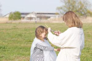 プロ用理美容はさみ国内生産本数No.1の家庭用髪はさみシゲルより先端のU字形状が安全設計でグッドデザイン賞受賞のミニ梳きはさみSG-313Tで前髪を切ってもらう女の子とお母さん